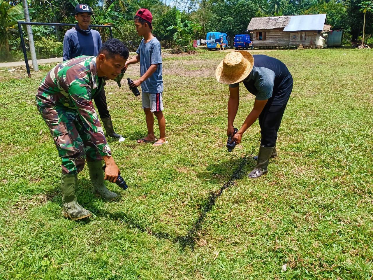 Anggota Satgas TMMD Asik Bantu Warga Membuat Line Lapangan Sepak Bola
